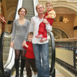 Family of four in shop and escalator — Stock Photo