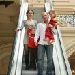 Family of four on escalator — Stock Photo