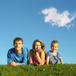 Family on herb under blue sky — Stock Photo