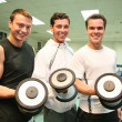 Three gym men with dumbbells — Stock Photo