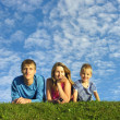 Stock Photo: Family on herb under blue sky