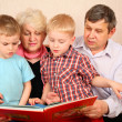 Grandparents with grandcgildren read book — Stock Photo