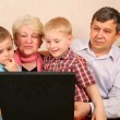 Grandparents with grandchildren with notebook — Stock Photo
