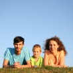 familjen på örten under blå himmel lögn — Stockfoto