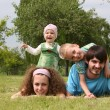 Family of four lies on grass 2 — Stock Photo