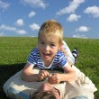 Son lie on ather on green grass — Stock Photo #3541483