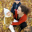 Mother with children on autumn leaves — Stock Photo #3541530