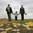 Walking family with autumn leaves and clouds — Stock Photo