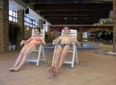 Couple on chairs and swimming pool — Stock Photo