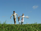Running family with child on meadow — Stock Photo