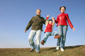Running family with child on spring meadow — Stock Photo