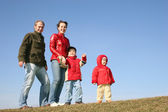Family of four on spring meadow 2 — Stock Photo