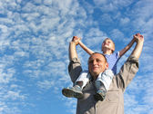Grandfather with grandson under cloudfield — Stock Photo