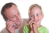 Grandfather and child with phones — Stock Photo