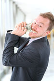 Hungry angry businessman with money — Stock Photo