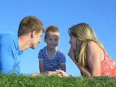 Family of three on grass — Stock Photo