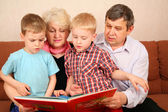 Grandparents with grandcgildren read book — Stok fotoğraf