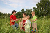 Family of four on meadow 3 (autoshoot from tripod) — Stock Photo