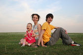 Family with baby sit on evening meadow — Stock Photo