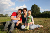 Family with two children sit on meadow and trees 2 — Stock Photo