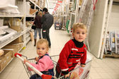 Children in shopingcart and couple — Stock Photo