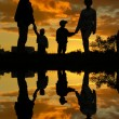 Royalty-Free Stock Photo: Family of four sunset 2 and water