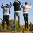 Jump boys on autumn bridge - Stock Photo