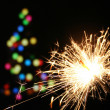 Sparkler and christmas tree — Stock Photo #3644072