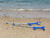 Crutches on beach — Stock Photo