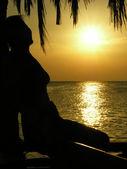 Woman sit. sunrise. palms. — Stock Photo