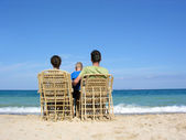 Behind family on easychairs on beach — Stock Photo