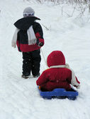 Child with baby on sled — Stock Photo