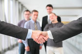 Shaking hands with wrists and business team 2 — Stock Photo