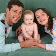 Family with baby on sofa — Stock Photo