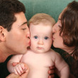 Parents kissing baby — Stock Photo