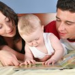 Family with baby read book 2 — Stock Photo
