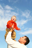 Baby in sky on fathers hands — Stock Photo