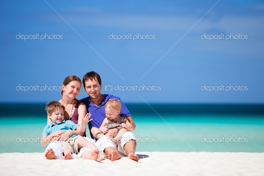 Family of four having fun on tropical beach — Stock Photo #3587167