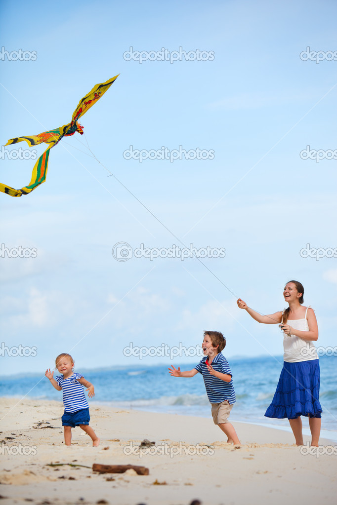 Young mother and two kids running with kite on the beach — Stock Photo #3587485