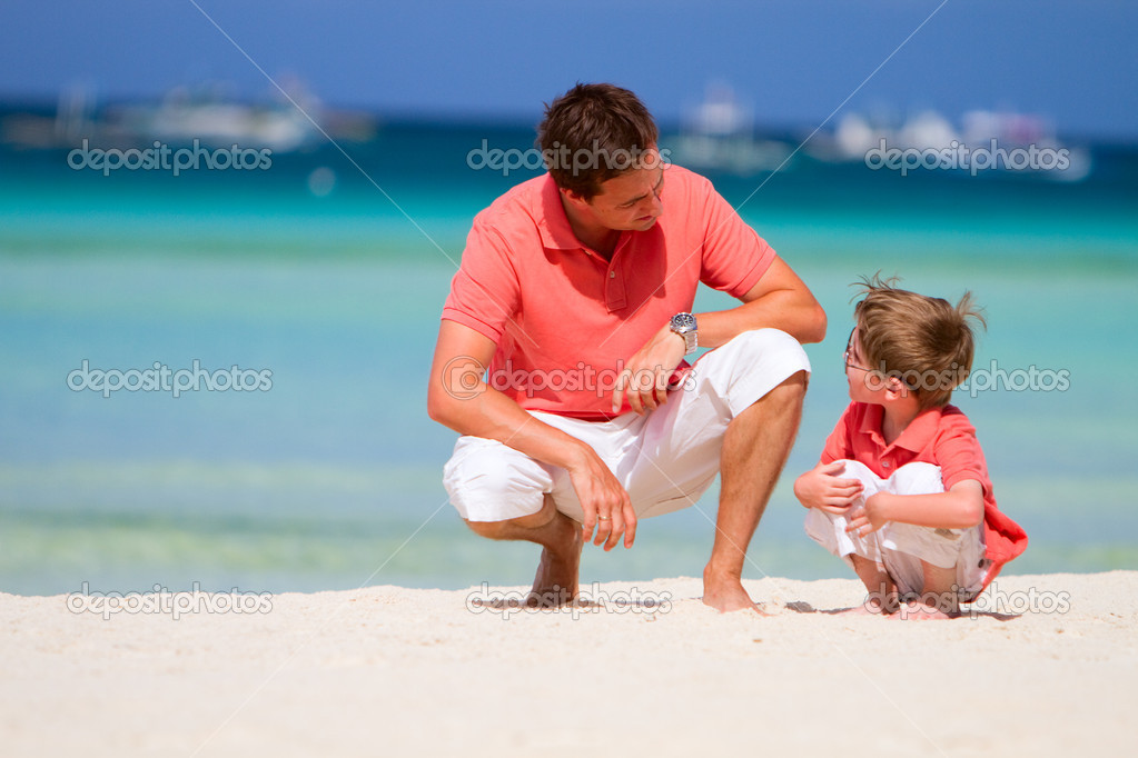 Father and son on tropical white sand beach  Stock Photo #3593737