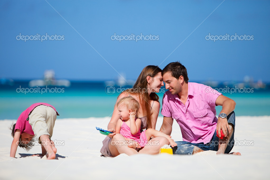 Family of four having fun on tropical beach  Stock Photo #3646068