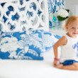 Adorable smiling toddler girl in bedroom - Stock Photo