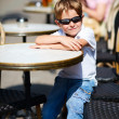 Boy sitting in outdoor cafe — Stock Photo