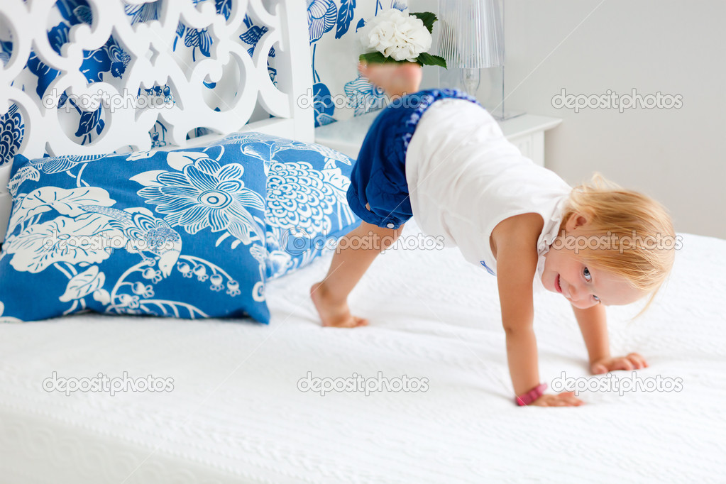 Portrait of adorable playful toddler girl jumping on bed in nicely decorated bedroom  Stock Photo #3659045