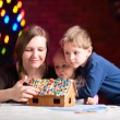 Mother with kids making gingerbread house — Stock Photo