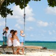 Family swinging on tropical beach - Stock Photo