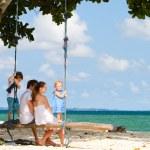 Family swinging on tropical beach — Stock Photo