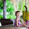 Royalty-Free Stock Photo: Toddler girl outdoors with bunch of bananas