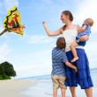 Family flying kite on tropical beach — Stock Photo #3697074