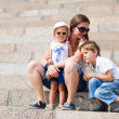 Mother and two kids sitting on steps — Stock fotografie